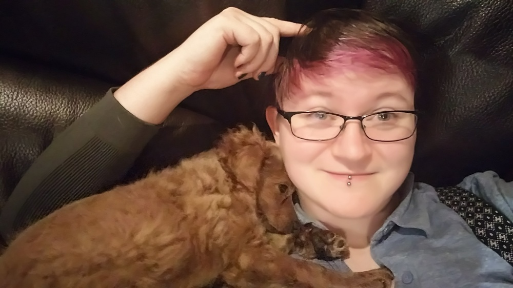 Picture of Hilda cuddling with a small brown puppy
